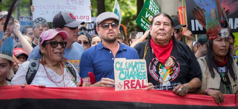 Leonardo DiCaprio holding a placard on Climate Change