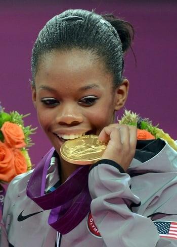 Gabby Douglas bites the gold medal