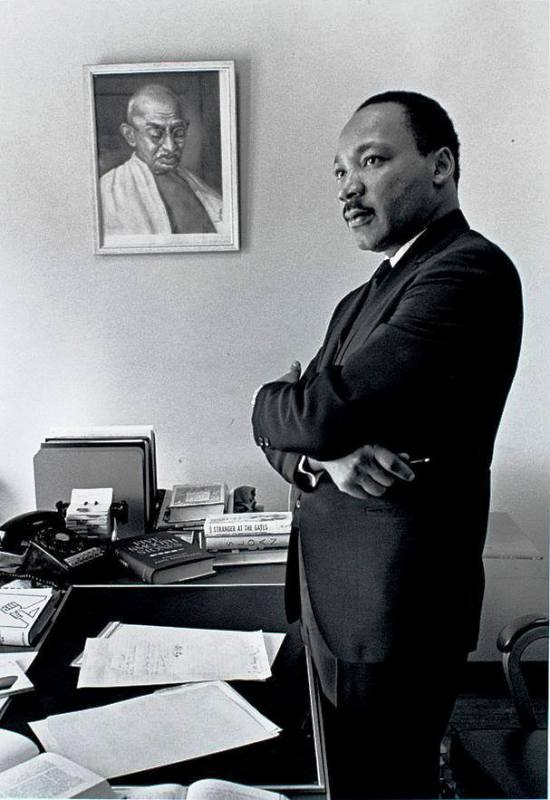 Martin Luther King Standing In Front of A Portrait of Mahatma Gandhi