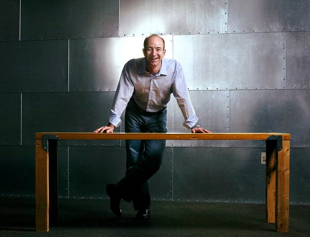 Jeff Bezos posing with the table that he had made from a door