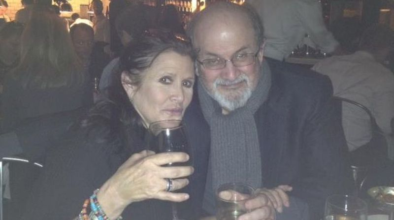Salman Rushdie while holding a glass of alcohol