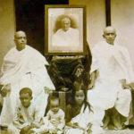 C. A. C. Bhaktivedanta Swami Prabhupada's Family, From Left Swami Prabhupada (Sitting), Portrait of His Father Gaur Mohan De (Middle), His Brother Krishna Charan (Sitting), His Son Prayag Raj (Sitting Frontside Left), His Second Son (Sitting Middle), His Daughter Sulakshman (Sitting Frontside Right)