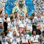 Luka Modric with his Real Madrid teammates holding Champions League Trophy in 2018