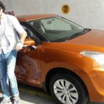 Deepak Wadhwa poses with his Maruti Suzuki Baleno car