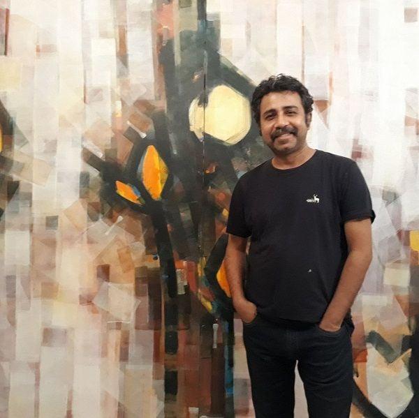 Pankaj Jha with his painting in backdrop
