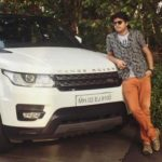 Syed Aman Mian Sharma poses with his Range Rover car