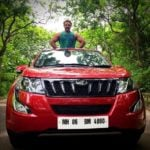 Devdatta Nage poses with his Mahindra XUV500 car