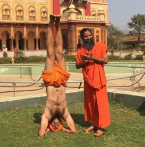 Shivendraa Om Saainiyol doing yoga in front of Baba Ramdev