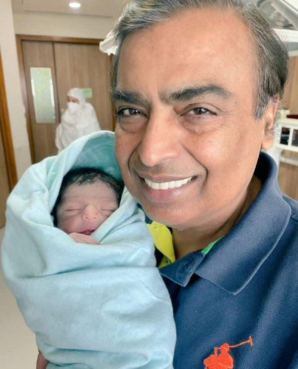 Mukesh Ambani holding his newborn grandson in his lap