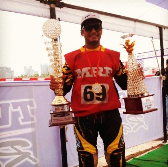 Aravind KP posing with awards at MRF Championship