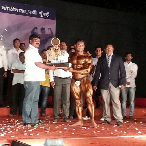 Jagdish Lad receiving a trophy in a body building competition