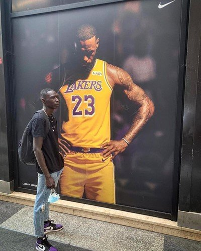 Khaby Lame posing in front of a poster of LeBron James
