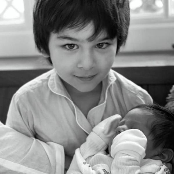 Taimur holding his younger brother Jeh in his lap